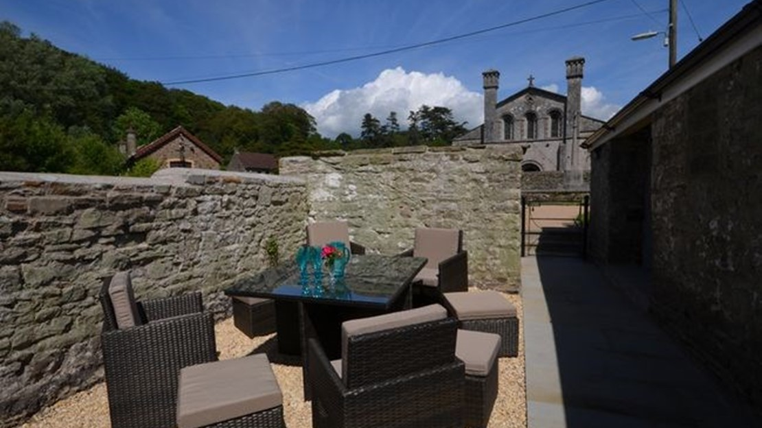 Patio area with seating, BBQ and view towards Margam Abbey